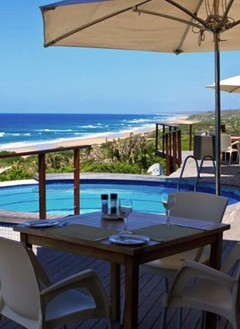 Beach view with dining area and swimming pool in the foreground, at Massinga Beach